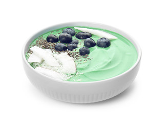 Bowl of spirulina smoothie with blueberries, coconut and chia seeds isolated on white