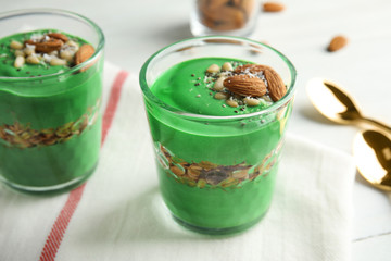 Glass cups of spirulina smoothie on table