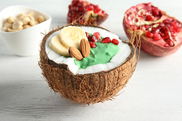 Yummy spirulina smoothie in coconut and pomegranate on wooden background, closeup