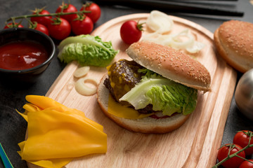 Homemade hamburger with fresh vegetables served on a wooden tray. Homemade preparing concept.