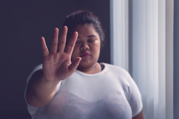Obese woman showing hand gesture to stop