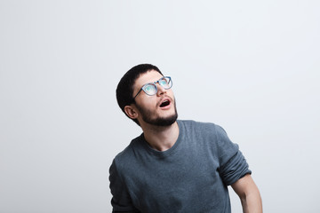 Portrait of shocked young man with glasses over white studio background
