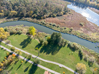 natural landscape aerial top view. city park with bushy autumnal trees, green lawns, bikeway and river