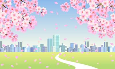 桜の木の枝とビル街へと続く草原の一本道