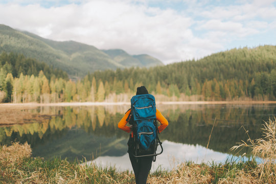 A hiking woman looking out at a beautiful view of mountains and a calm lake.