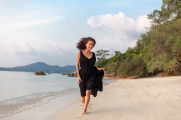 Young beautiful happy sensual woman in a stylish dress joyfully runs along the beach, beauty and fashion, leisure and travel concept