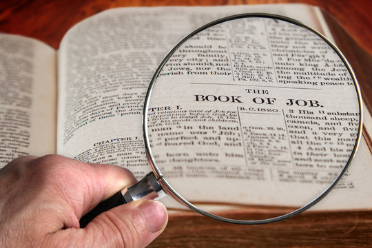 Magnifying Glass on Famous Bible Chapter of Job, a King James Bible which is Public Domain.