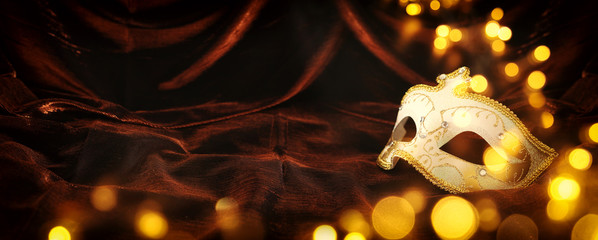 Photo of elegant and delicate gold, white venetian mask over dark velvet and silk background.