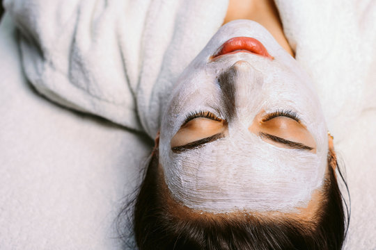 Beautiful caucasian girl resting with closed eyes in a spa center while on her face is applied a white mask in medical purposes for skin care.