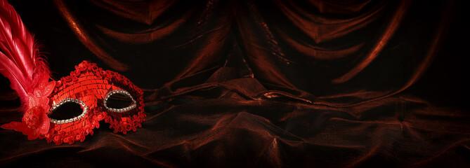 Photo of elegant and delicate red venetian mask over dark velvet and silk background.