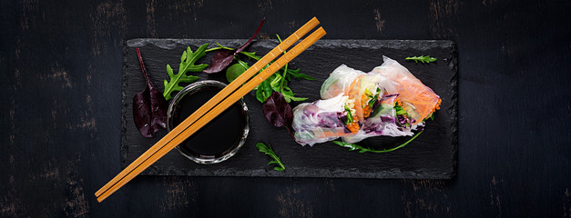 Fototapeta Vegetarian vietnamese spring rolls with spicy sauce, carrot, cucumber, red cabbage and rice noodle. Vegan food. Tasty meal.  Top view, flat lay, banner obraz
