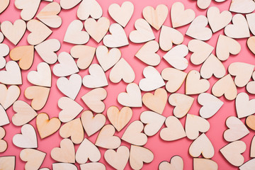 Wood hearts texture on pink background,