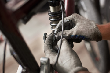 Cropped shot of male worker working in bicycle repair shop, repairing bike using special tool, wearing protective gloves