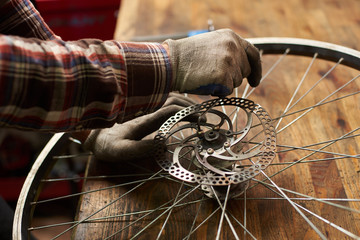 Cropped view of male mechanic working in bicycle repair shop, serviceman repairing bike wheel using special tool, wearing protective workwear and gloves