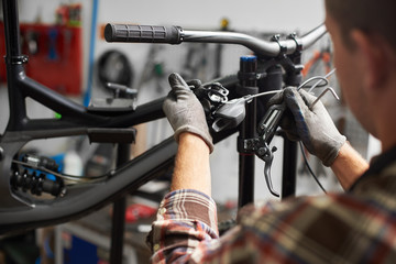 Cropped shot of professional repairman working in bicycle repair shop, mechanic repairing bike using special tool, wearing protective gloves