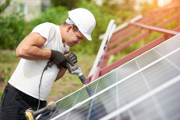 Profile view of technician connecting blue shiny solar photo voltaic panel to metal platform using electrical screwdriver on warm summer day. Stand-alone solar panel system installation concept.