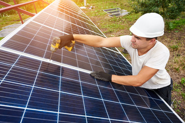 Professional technician working with screwdriver connecting solar photo voltaic panel to exterior metal platform under clear blue sky. Alternative renewable ecological green energy concept.