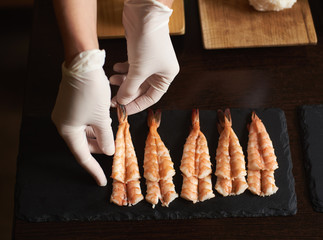 Closeup view of woman's hands in gloves are preparing shrimp for rolling sushi in restaurant