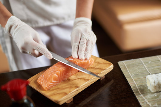 Close-up view of process of preparing rolling sushi. Hands in disposable gloves slicing salmon on wooden board