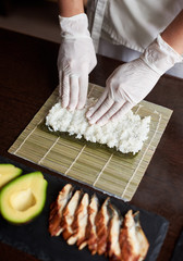 Close-up view of process of preparing rolling sushi. Nori and white rice on bamboo mat. Chef's hands touch rice. Chef starts cooking sushi. Eel and avocado