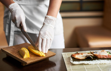 Closeup view of process of preparing rolling sushi. Hands in disposable gloves slicing omelet on wooden board
