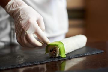 Close-up view of process of preparing rolling sushi at. Female hand in glove decorates roll with sliced avocado