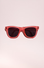 Red bright sunglasses on a pastel pink background. Summer time, party and vacations concept.