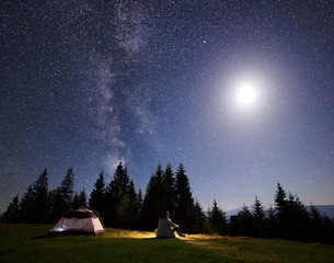 Camping night in mountain valley. Alone tourist sitting on grass at tent enjoying beautiful clear starry sky and fool bright moon over pine trees. Beauty of nature, tourism and traveling concept.
