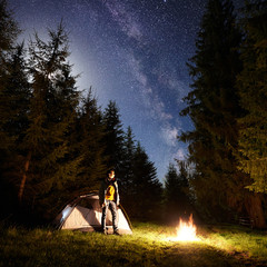 Camping site at night. Tourist tent on forest clearing and young hiker standing in front of burning campfire under dark blue starry sky on pine trees background. Beauty of nature and tourism concept.