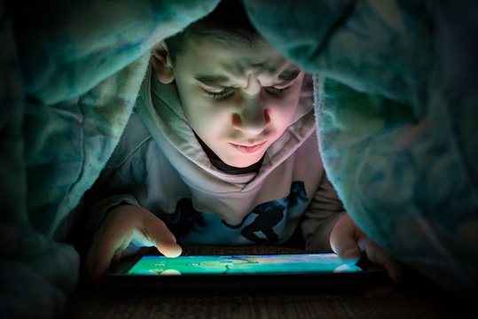 Child watching his tablet in the bed. Illuminated child face from device screen.