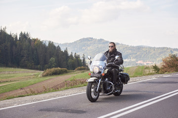 Handsome motorcyclist in black leather outfit riding cruiser bike on bright sunny summer day on background foggy distant green woody hills under morning sky.