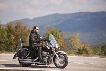 Side view of bearded long-haired motorcyclist in sunglasses and black leather clothing riding cruiser motorcycle along narrow asphalt path on sunny day