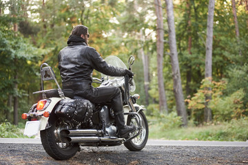 Back view of bearded biker in black leather clothing riding on cruiser motorbike on country roadside on background of empty straight asphalt road and green trees bokeh foliage.