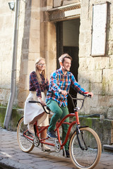 Active happy tourist couple, bearded man and smiling long-haired blond woman in white skirt and glasses cycling tandem bike along paved city sidewalk on bright sunny day by old ancient stone building.