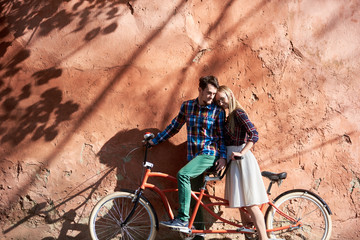 Young happy romantic tourist couple in casual clothing, bearded man and blond woman in glasses leaning together on double tandem bike on background of high red old crackled plastered wall.