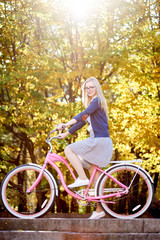 Attractive blond long-haired tourist girl in glasses, skirt and blouse posing on modern pink lady bicycle on lit by autumn sun park stairs on bright colorful golden bokeh trees background.