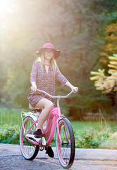 Slim happy smiling blond fashionable attractive woman in glasses, short dress and red hat riding lady bicycle along paved park alley on beautiful green and golden trees lit by bright sun background.