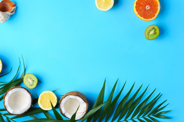 tropical beach, summertime travel, vacation, exotic fruits concept. palm leaves, coconut, citrus and kiwi slices on blue background. creative minimal idea, summer layout
