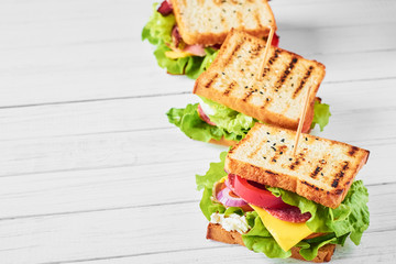 Three sandwiches with ham, lettuce and fresh vegetables on a white background