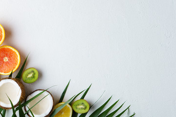 summer composition with exotic fruits and palm leaves on white background. summertime vacation, cocktail, tropical beach. creative layout, banner or poster template with copy space for text design