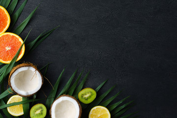 summer composition with exotic fruits and palm leaves on black background. summertime vacation, cocktail, tropical beach. creative layout, banner or poster template with copy space for text design