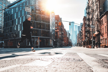 Young athlete running through the New York streets. Sporty man fast running early morning in sunny day through urban city