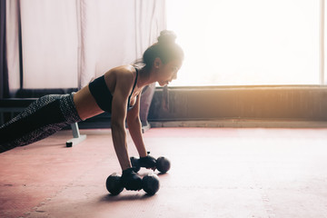 Young asian woman doing push-ups on dumbbell in a gym.