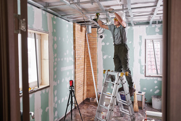 Room repair. Interior finish. young builder makes a plasterboard ceiling, standing on a stepladder