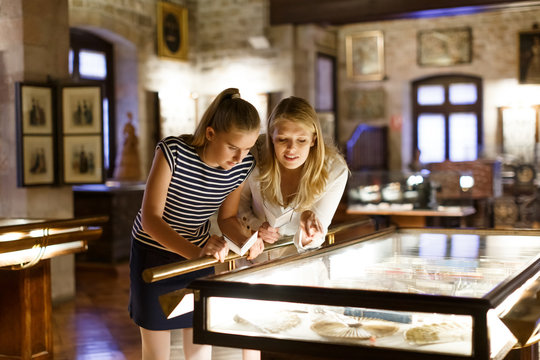 Girl with woman looking with interest at art objects under glass in museum