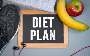 Chalkboard with sport shoes, fruits, towel and diet plan