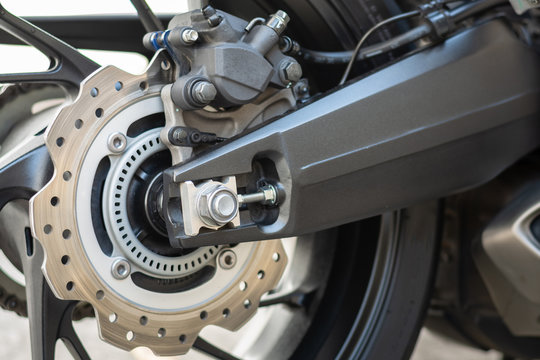 Closeup detail of sport racing motorcycle wheel and ABS brakes system with aluminium swingarm 220 mm rear disc 1 piston caliper stopping power ABS fitted as standard.