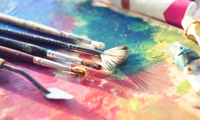 Brushes and palette knife lie on the palette with tubes of oil paint