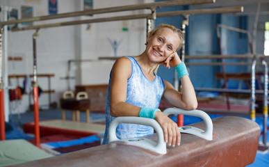 Positive mature woman acrobat in bodysuit exercising gymnastic action