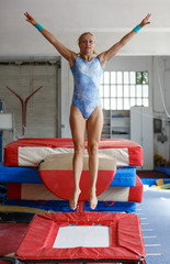 Woman gymnast in bodysuit jumping at  trampoline in sport gym